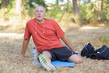 middle age sitting runner outside doing stretch in forest