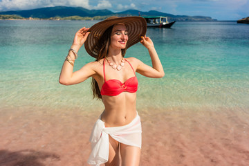 Fashionable young woman with a perfect body smiling while posing outdoors during summer vacation at Pink Beach, pink, in Komodo Island, Indonesia