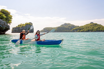 Two women are mother and daughter. Travel by boat with a kayak under sky summer around Ko Phi view the beautiful nature of the sea and island, Mu Ko Ang Thong National Park, Surat Thani, Thailand