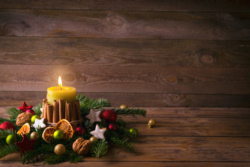 Christmas or advent background  -  Burning candle with natural decoration on rustic wood