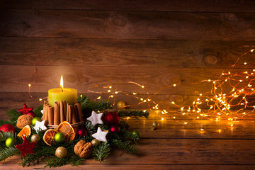 Festive Christmas or Advent Background  -  Burning candle with natural decoration on rustic wood