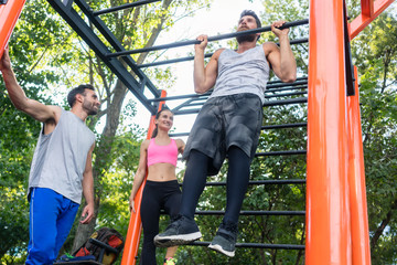 Low-angle view of a strong young man doing chin-up repetitions for the upper-body during calisthenics workout, with his friends in a modern outdoor fitness park