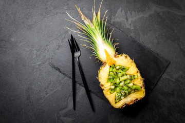 Holiday diet concept or tropical Christmas menu concept. Christmas tree made from pineapple and kiwi on slate board. Ideas for Christmas New Year menu.