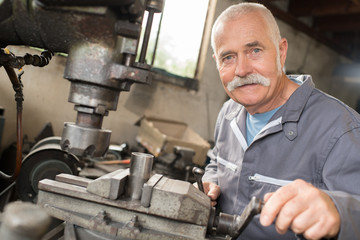 happy senior worker operates metalworking machine