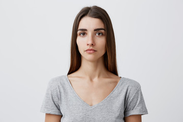 Close up of young handsome charming caucasian girl with long brown hair in gray t-shirt looking in camera with serious face expression. Woman getting photo for passport.