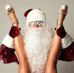 Bad santa claus in snow flakes sunglasses honding young sexy naked legs woman