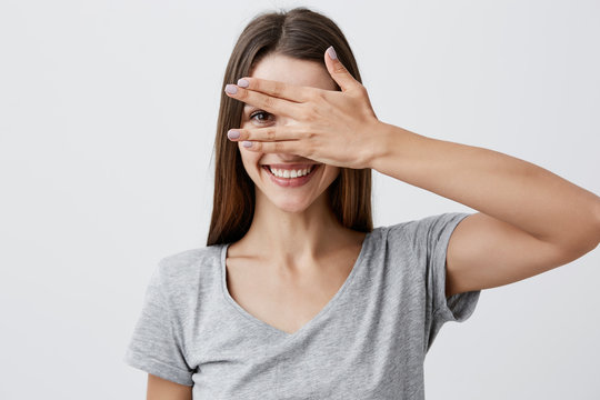 Close up portrait of beautiful joyful young caucasian student girl with dark long hair in trendy gray t shirt smiling with teeth, clothing eyes with hand, looking through finger with one eye.