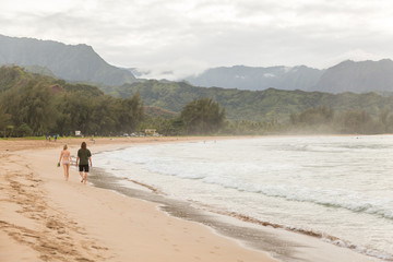 Young couple walking along Hanalei beach, Hawaii