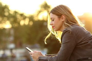 Woman reading text in a smart phone at sunset
