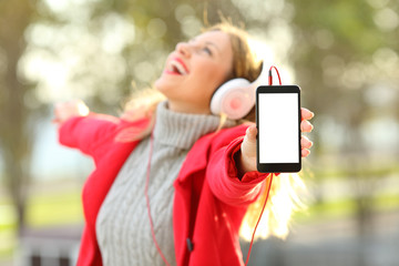 Joyful girl listening music and showing phone screen in winter