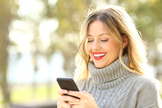 Happy woman reading text on phone in winter