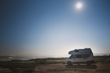 Motorhome RV and campervan are parked on a beach. Motor home caravan are parked on a parking space for RV van vehicles by Aegean sea in Greece. Night scenery.