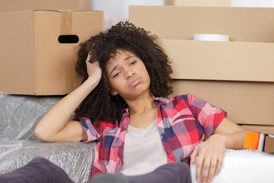 frustrated woman sitting by cardboard boxes in new house