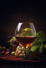 Cognac In Glass, Grapes And Vine, Old Wooden Background, Selective Focus