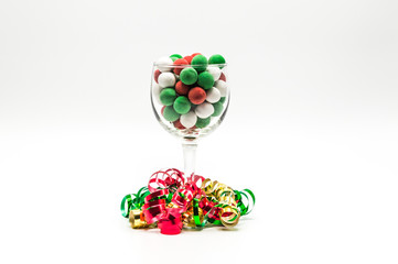 wineglass filled with colorful Christmas candy surrounded by bright colored curling ribbon isolated on a plain background