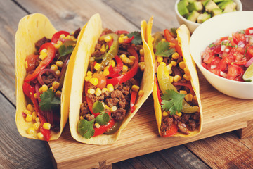 Three Mexican tacos with minced beef and mix vegetables on old rustic table. Mexican dish with sauces salsa in bowl and avocado. Spicy and hot street food. Close-up