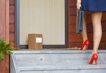 Woman arrives home after work to delivery parcel with label at door
