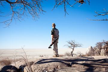 Senior man holding a tripod overlooking the makgadikgadi salt pans in Botswana