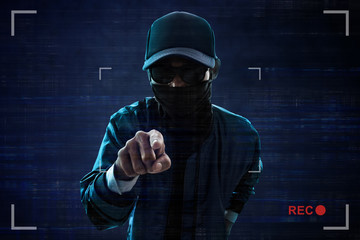 Unknown hacker pointing at camera