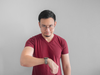 Angry and unpleasant face of man is looking at his watch waiting for someone.