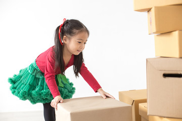 Attractive Asian Girl try to move a box at home. Kid holding Box with Attractive smiling. Kid with Happy Emotion.