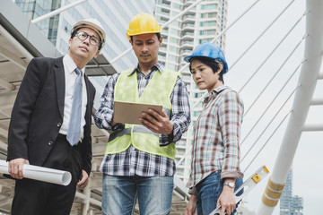 Multiethnic business man or engineer or architect and technician with business partner on meeting and discussion while using on digital tablet, smartphone on modern city. Startup or teamwork concept.