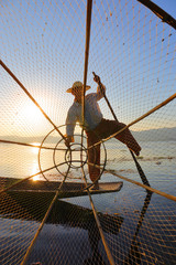 Fisherman silhouette with net at Inle lake