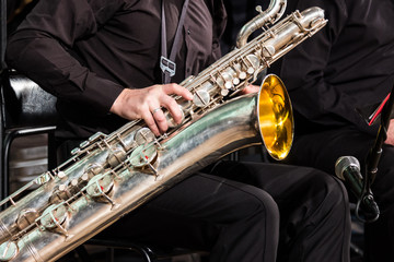 The saxophonist of the jazz collective sits on a chair and puts a baritone saxophone on his knees.