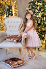 Christmas celebration. Cute little girl in a beautiful dress sitting near the Christmas tree. Christmas miracles. Luxurious Christmas decoration.