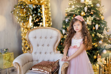 Christmas celebration. Cute little girl in a beautiful dress sitting near the Christmas tree. Christmas miracles. Luxurious Christmas decoration.