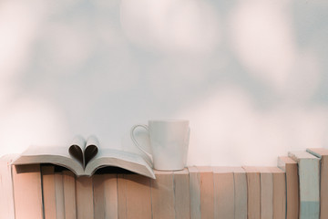 Open book in heart shape with a cup of coffee and books on the shelf - Retro vintage filter effect
