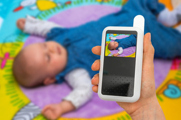 Mother is holding baby monitor camera for safety of her baby