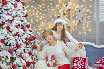 Christmas Family together cellebrating holiday New Year daughter and mother close to white xmas tree with snow and red balls toys