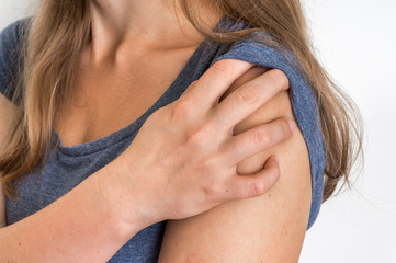Woman with shoulder pain is holding her aching arm