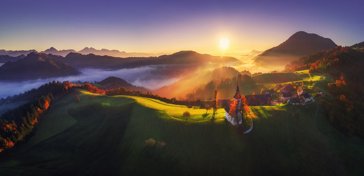 Aerial sunrise view of Saint Tomas church, Slovenia. Autumn landscape.