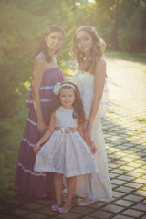 Amazing Brunette blond chestnut blue eyes sisters girls wearing stylish white purple dress enjoying vacation together spring sunny day in garden meadow on fresh grass lovely smiling