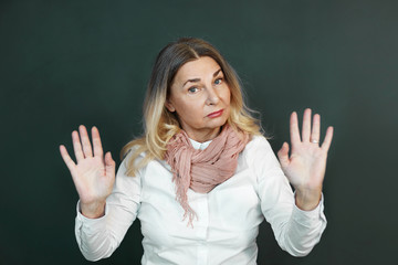 Portrait of confident determined elderly woman with blonde grey hair making stop gesture, showing open palms at camera, meaning: Stay away from me, Don't come close. Body language, signs and symbols