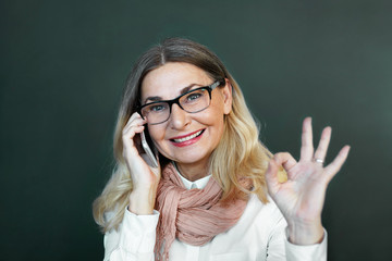 Attractive confident mature businesswoman with loose blonde hair and stylish scarf wrapped around her neck smiling, making ok gesture, having successful business negotiations using mobile phone