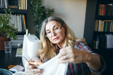 Picture of focused serious middle aged European woman sewing, using stitching machine at home, sitting at her workplace. Elderly female dressmaker holding fabric, scissors and measuring tape