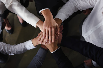 Business people joining hands in the office. concept of teamwork and partnership