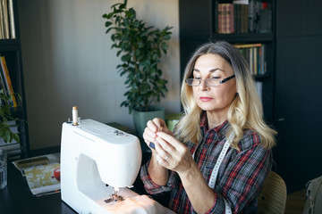 Picture of serious confident blonde retired woman dressmaker in stylish eyewear making custom clothing for women, sitting at her workplace, busy stitching dress using modern white sewing machine