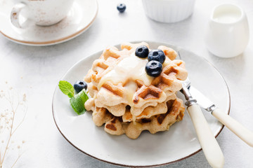 Belgian waffles with cream honey and blueberries on white plate. Bright breakfast image