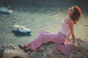 Charming Sensual beautifull lady girl woman with red flame hair wearing fancy fashion pink clothes posing sitting rock sand mountain wth port boats on background Adoring scene of sea mermaid