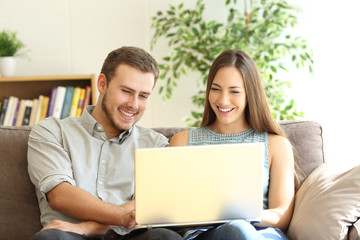 Couple using a laptop together on a couch