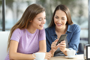 Two friends sharing on line content in a smart phone in a bar