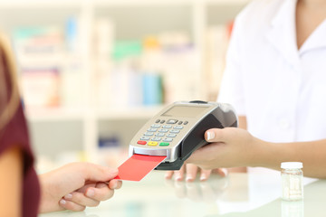 Pharmacist hands charging with credit card reader