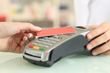 Woman paying with a contact less credit card in a shop