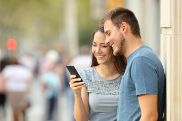 Couple watching on line media in a smart phone on the street