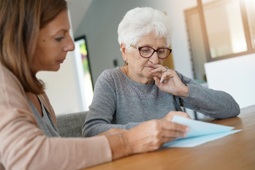 Home assistant helping elderly woman with paper work