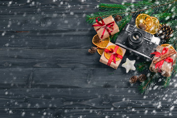 Christmas background with fir, gifts and camera. On a wooden background. Top view Free space for text.